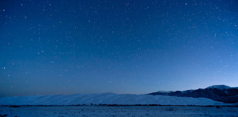 Pre-dawn night sky above the snow covered Great Sand Dunes National Park and Preserve.