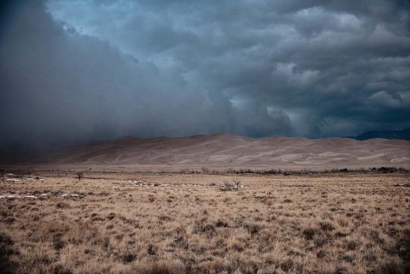 A powerful winter storm with snow,  thunder and lightning moves from the San Juans, sweeps across the San Luis Valley and engulfs the dunes in snow.