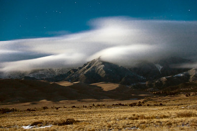A blustery moonlit night  spreads clouds  across the sky  above the dune field and the Sangre de Cristo Mountains at the Great Sand Dunes National Park and Preserve.
