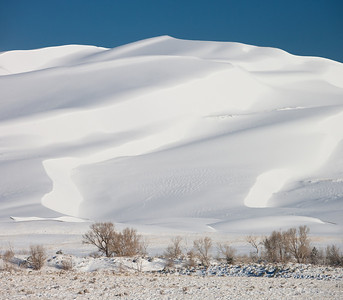 Panoramic image of snow covered sand dunes in Great Sand Dunes National Park and Preserve after an overnight storm. Two vertical images were stitched to create this image. If you click on the image and then select the X3 version you will be able to see the small spec of a person at the top of the dune.