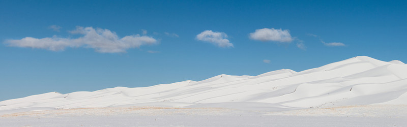 Panoramic image of snow covered sand dunes in Great Sand Dunes National Park and Preserve after an overnight storm.