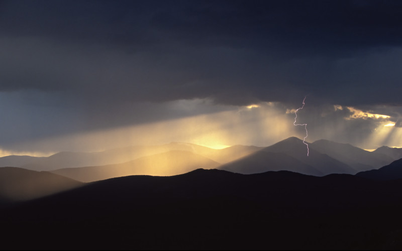 Lightning strikes through the god rays of sunset near Mount Evans, Colorado.