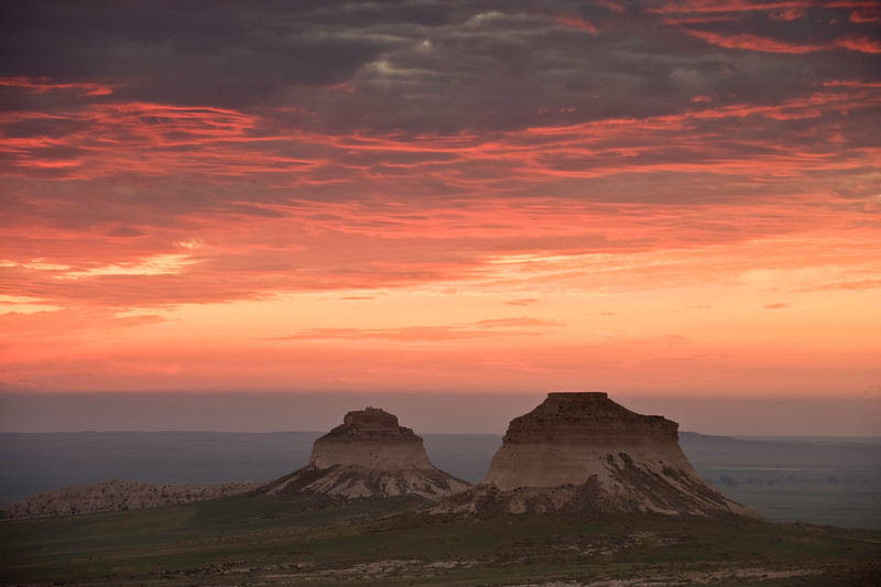 A colorful orange sunrise greets the east and west buttes at Pawnee Buttes, in Pawnee National Grasslands, north of Greeley Colorado.
