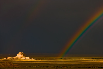 A vibrant rainbow arches from the golden prairie into a dark, stormy dark sky at Pawnee Buttes, in Pawnee National Grasslands, north of Greeley Colorado.