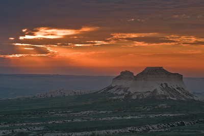 A colorful orange sunrise spreads across the sky to greet the east and west buttes at Pawnee Buttes, in Pawnee National Grasslands, north of Greeley Colorado.