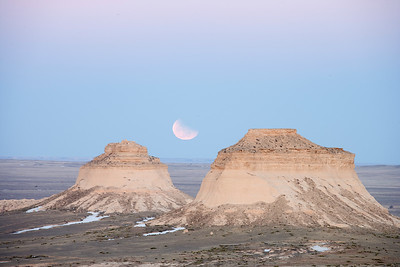 Full moon rising in partial eclipse over Pawnee Buttes, in Pawnee National Grasslands, north of Greeley Colorado.
