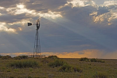 God rays streak from clouds behind a water station windmill at Pawnee Buttes, in Pawnee National Grasslands, north of Greeley Colorado.