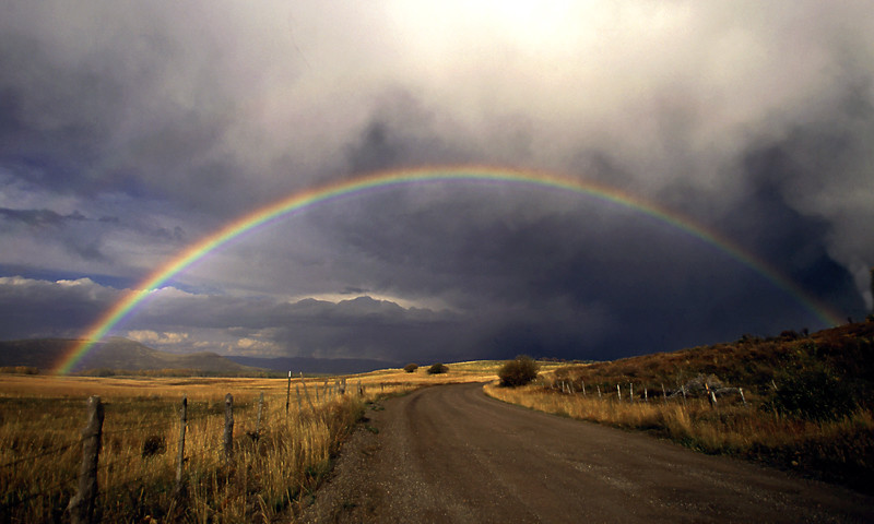 A vibrant rainbow arches across Last Dollar Road between Telluride and Ridgway, Colorado.