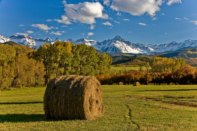 Hay bales create a bucolic Fall view of Mount Sneffels on Dallas Divide outside Ridgway, Colorado.