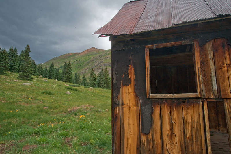 Storm clouds and soft light bring out the textures of the wall of an abandoned cabin at the Animas Forks mining town near Silverton Colorado