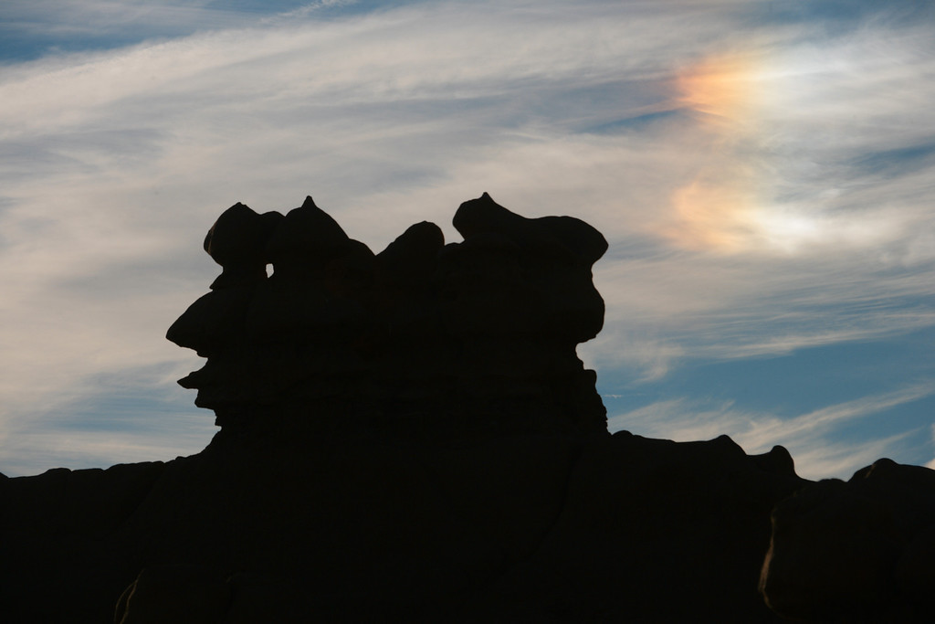 Sunlight reflecting off ice crystals in the atmosphere cause a 'sun dog' to  forms above hoodos in Goblin Valley State Park near Hanksvillle and Green River, Utah.