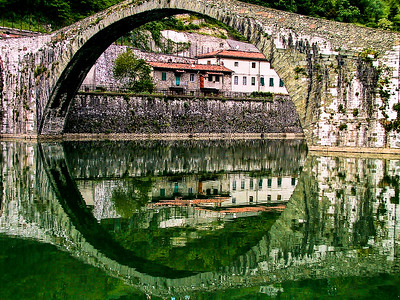 Reflection of an old vilage and bridge, Tuscany