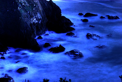 © Joseph Dougherty. All rights reserved.   Moonlight on the waves at the base of a sheer rocky cliff; Mendocino County, California.