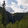 The waterfall and mountain rise over the trees