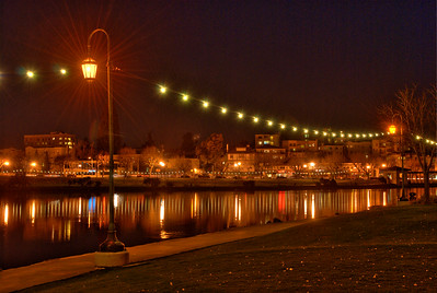 """Lake Merritt's """"Necklace of Pearls"""" lights reflected in the water at night; Oakland, Alameda County, California."""