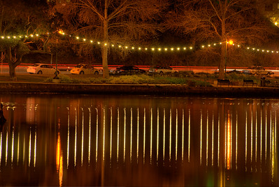"""© Joseph Dougherty.  All rights reserved.   Lake Merritt's """"Necklace of Pearls"""" lights reflected in the water at night; Oakland, Alameda County, California."""