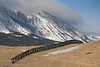 A snow fence running across the hills below the Livingstone Range in Southern Alberta