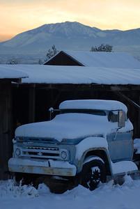 Old truck under snow, on farm near Reno, Nevada.
