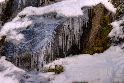 © Joseph Dougherty. All rights reserved.   Icicles hang from the cliff face along a waterfall in the Sierra Nevada.