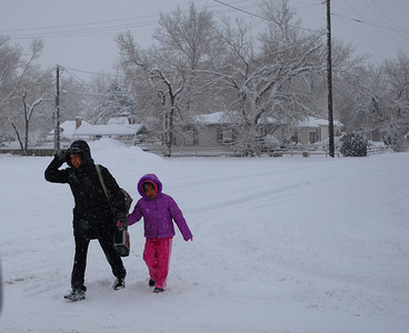 © Joseph Dougherty. All rights reserved.   A mom walks her daughter to school through falling snow.