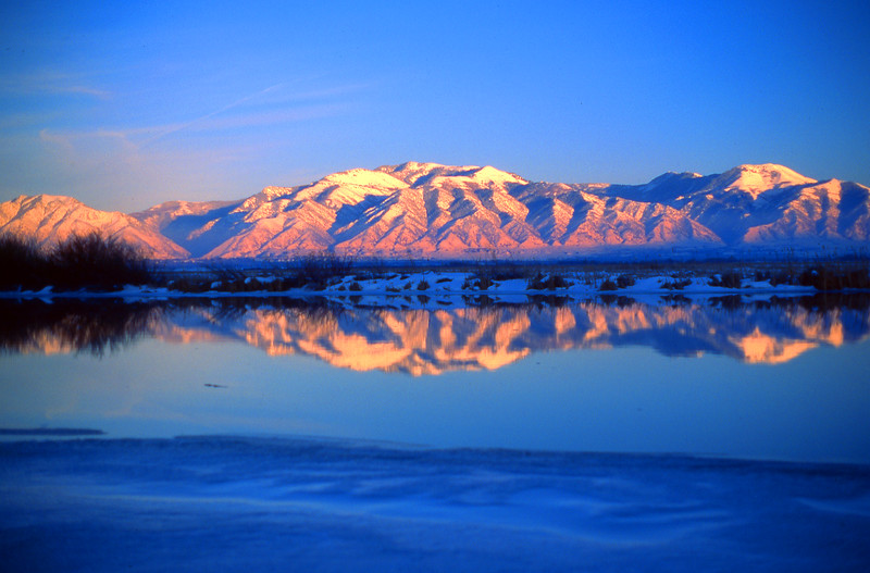 Mt. Logan and Naomi Peak reflect in the partially frozen Bear River.  near Benson, UT<br /> <br /> © Kirk Sagers