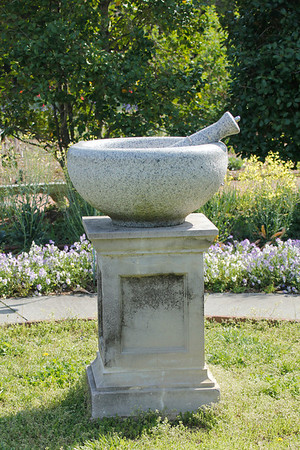 mortar and pestle statue in the medicinal garden