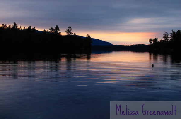 A calm April sunrise warms Squam Lake.
