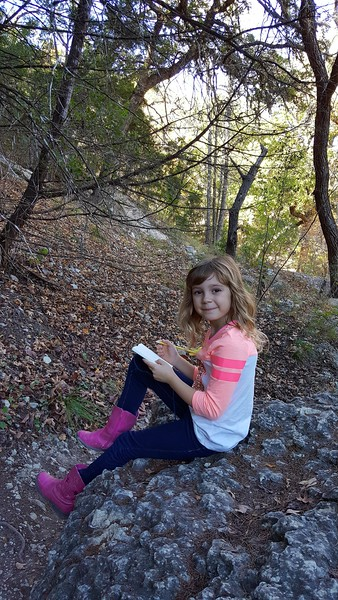 Laney making notes in her notebook, while on the hike