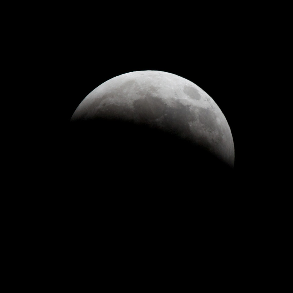 23:14 Monday Dec 21, 2010: Start of a lunar eclipse.  Here the moon is halfway into the Earth's penumbra (outer shadow).