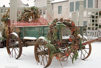An old wooden wagon covered by fresh-fallen snow sits in front of the Oswald Visitor Center.