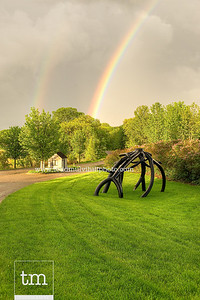 A rainbow appears over a Steel Roots sculpture as the setting sun breaks through the storm clouds.