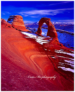 Delicate arch at sunset. This sandstone really lights up at sunset. This was taken with 4x5 velvia sheet film with a polarizer. That helps the color also.