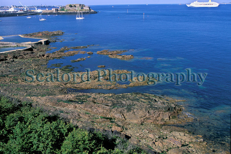This is a view of the rocky shore at La Valette on Guernsey's east coast at the time of low water during a neap tide.  This image was taken from Clarence battery, which is an 18th and early 19th century fort.  The Oriana cruise ship lies in the Little Russel off St. Peter Port harbour. Castle Cornet is on the far side of Havelet Bay. The bathing pools border the northern edge of La Valette.  I call the broad gully filled with seawater(horizontal in the image) 'seaweed gully'. The two isolated outcrops of bedrock above the centre of the image are separated by a short gully (horizontal in the image) that runs from east to west. I call this gully 'overhang gully'.  To the east of 'overhang' gully (to the right in the image) there is a cobble field which provides a home for many mobile species such as fishes and crabs. In the extreme upper right corner of the image a northern part of Herm Island is visible.  Photograph taken on the 8 June 2001.<br /> File No. 33-482<br /> ©RLLord<br /> fishinfo@guernsey.net