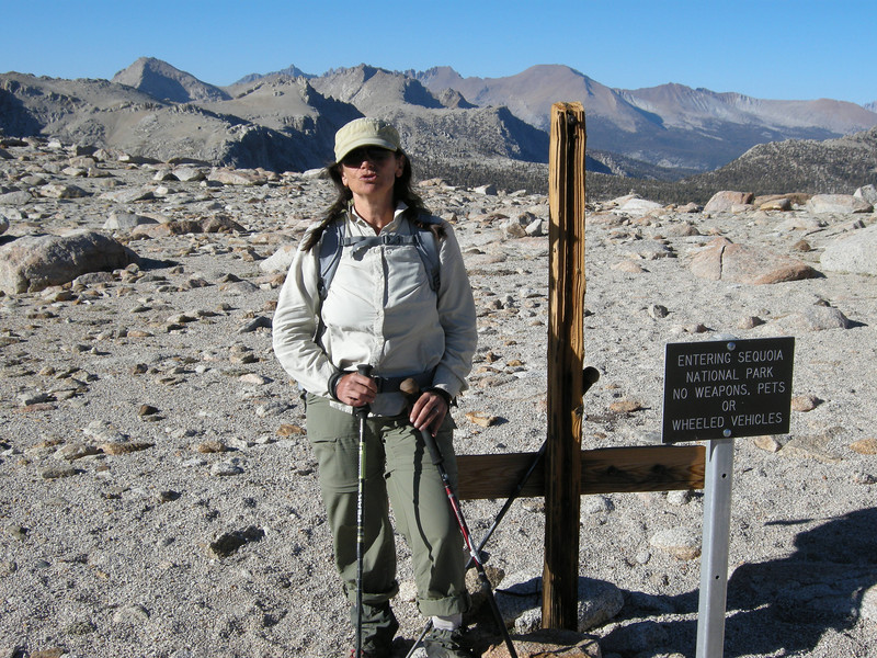 "Through the crux, and atop Shotgun Pass, with the Kaweah Peaks beyond. The pass is about 11,500 feet. The red bulk of Mount Kaweah, just above the top of the wooden post, rises to 13,802 feet.<br /> <br /> The ""welcoming"" National Park sign was and is now obsolete, as weapons ARE now allowed in National Parks, thanks to a Supreme court ruling; the Parks still prohibit hunting, however."