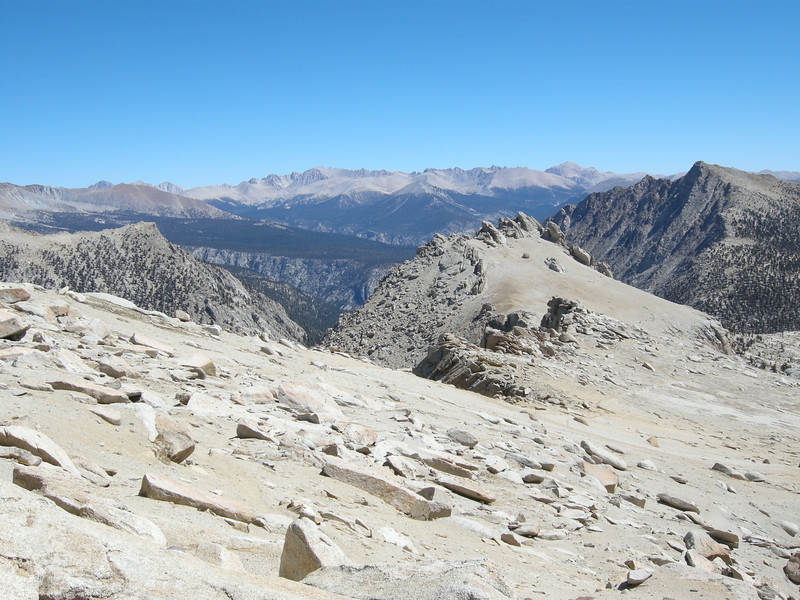 The final sandy ascent of the Franklin Pass trail on the east side, with the peaks of the Sierra Crest on the skyline and the wooded Chagoopa Plateau in the middle distance.