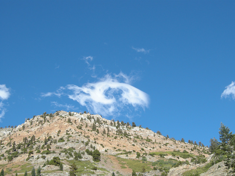 A swirling vortex of wind showed itself momentarily high above us as it twisted this small cloud into a near-circle.