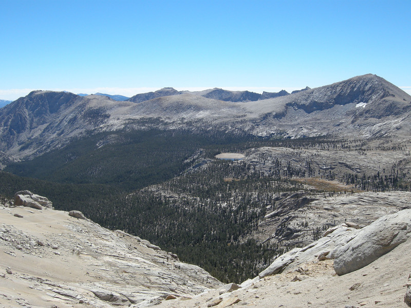 View to the southeast, with the peaks of the southern boundary of Laurel Basin just peeking above the ridge. An oval brown area near the center of the photo is the lakebed of an un-named lake that typically drains nearly dry by late-season.