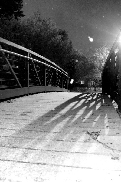 Bridge on Gallagator Trail in black and white, the white spots are snowflakes reflecting the flash.  Bozeman, MT<br /> <br /> © Kirk Sagers