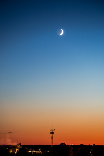 A September sliver moon sits in the sky just after sunset.  The planet Mars by its side and a large antenna on the earth below.