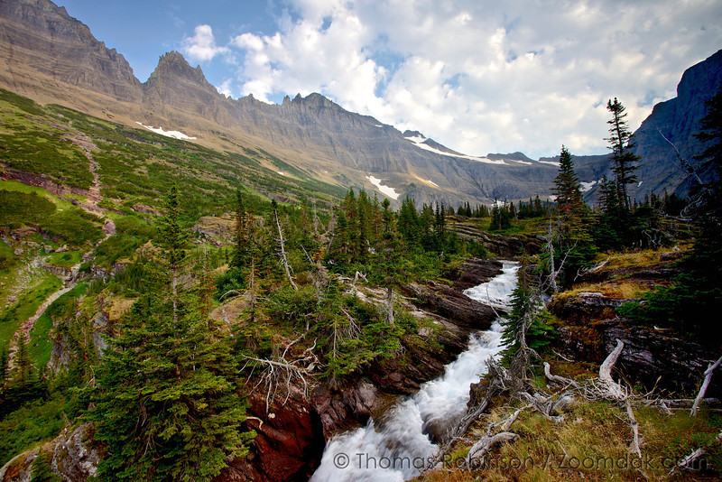 The beginning of Pyramid Creek flows out from Margaret Lake with the continental divide above. A mountain stream in Glacier National Park. Glacier is home to 2,865 miles of streams.