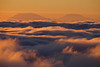 Sunlight dances across the sea of clouds at sunrise with Mt. St. Helens and Mt. Adams in the background.
