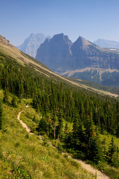 The trail to the continental divide at Stoney Indian Pass leads through the woods with Pyramid Peak and Mount Merritt standing strong behind. Glacier National Park, Montana.