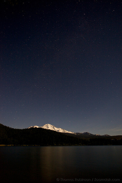 Mt. Shasta catches the moon light under a starry sky reflected off Lake Siskiyou