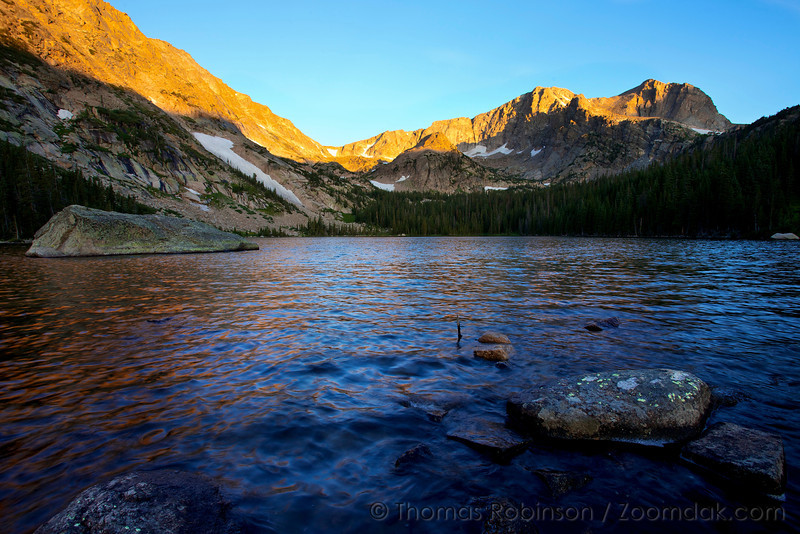 The sun comes up on Boulder-Grand Pass and Mount Alice above Thunder Lake in Rocky Mountain National Park.