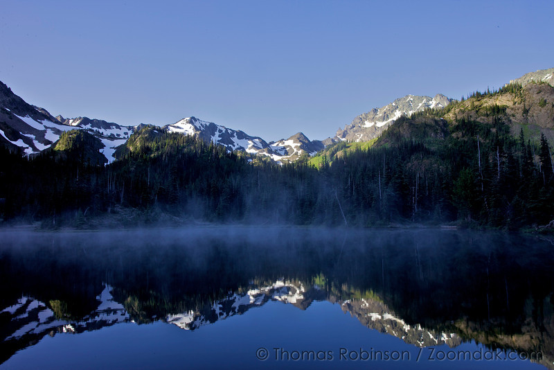 The stretch of mountains from Mount Fricaba to Mount Deceptions catch the morning light as mist lifts off Royal Lake.