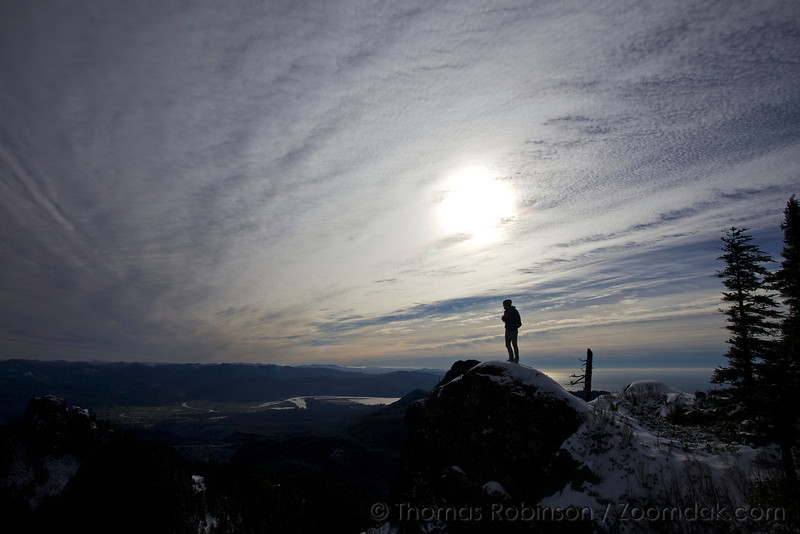 Perry Broderick stands silhouetted on top of Angora Peak looking south over the Cascade Range.