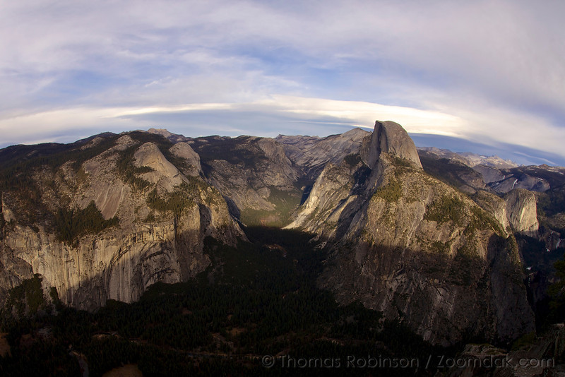 Yosemite Valley lays stretched below Glacier Point with Half Dome - the icon of Yosemite.