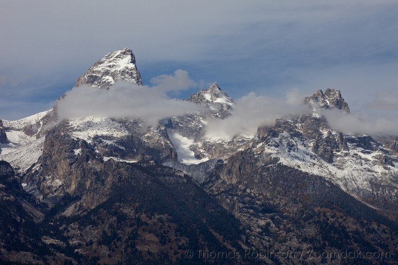 The Grand Teton mountain peaks out of the clouds.