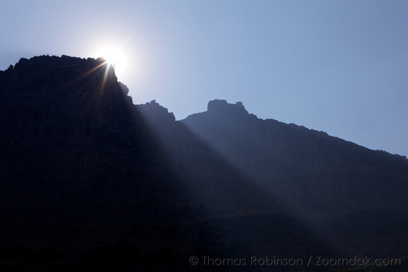 The sun crests over Pyramid Peak with God beams shining down to the valley below. An image of hope.