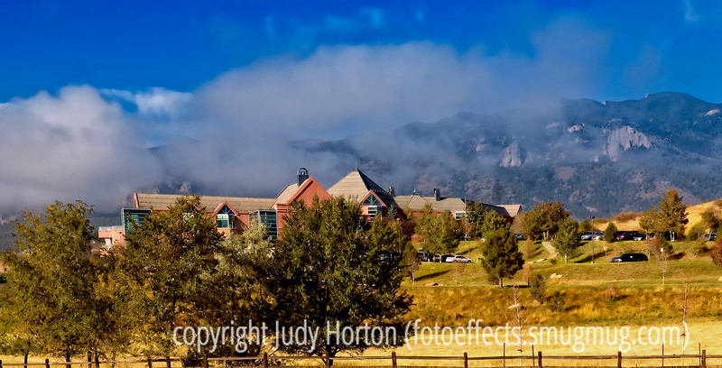 A low foggy group of clouds hangs over the mountains of the Front Range in Colorado.